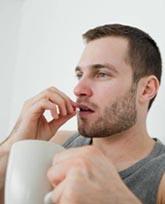 мужчина держит стакан и собирается выпить таблетку для потенции